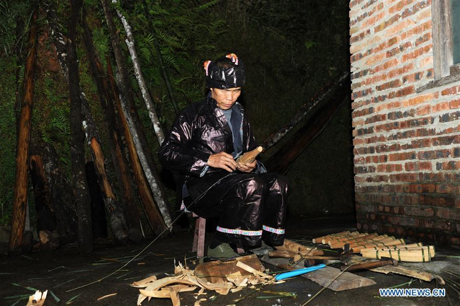 Craftsman Liang Jianzhong whittles a sound hole on the tube of Lusheng at Jinying Village in Congjiang County of Miao and Dong Autonomous Prefecture of Qiandongnan, southwest China\'s Guizhou Province, on Oct. 16, 2018. Lusheng is an ethnic musical instrument with multiple bamboo pipes set into a wooden blowing tube. It is popular among the people of some ethnic groups living in southwestern China. Jinying Village, known for making Lusheng, still keeps the traditional Lusheng making techniques which include over 30 steps such as choosing material, installing reed and whittling sound hole. People often play the Lusheng while gathering to celebrate some major festivals. (Xinhua/Yang Wenbin)
