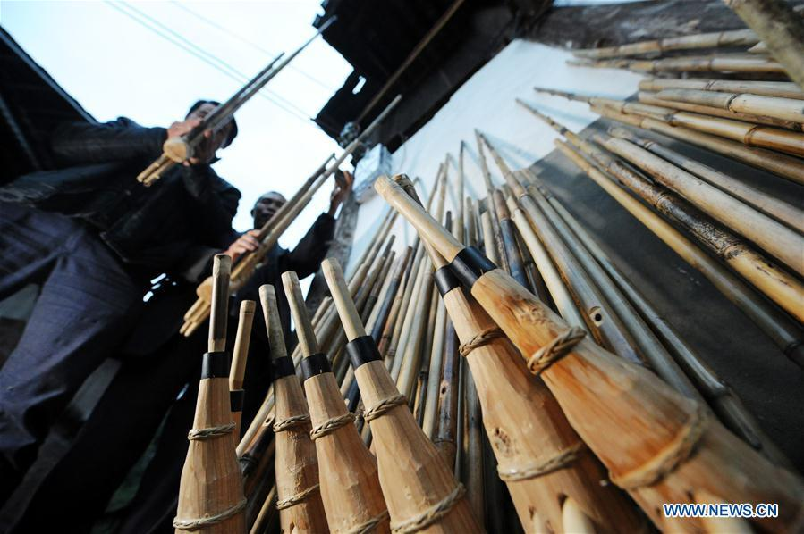 Craftsmen test the tone of finished Lushengs at Jinying Village in Congjiang County of Miao and Dong Autonomous Prefecture of Qiandongnan, southwest China\'s Guizhou Province, on Oct. 16, 2018. Lusheng is an ethnic musical instrument with multiple bamboo pipes set into a wooden blowing tube. It is popular among the people of some ethnic groups living in southwestern China. Jinying Village, known for making Lusheng, still keeps the traditional Lusheng making techniques which include over 30 steps such as choosing material, installing reed and whittling sound hole. People often play the Lusheng while gathering to celebrate some major festivals. (Xinhua/Yang Wenbin)