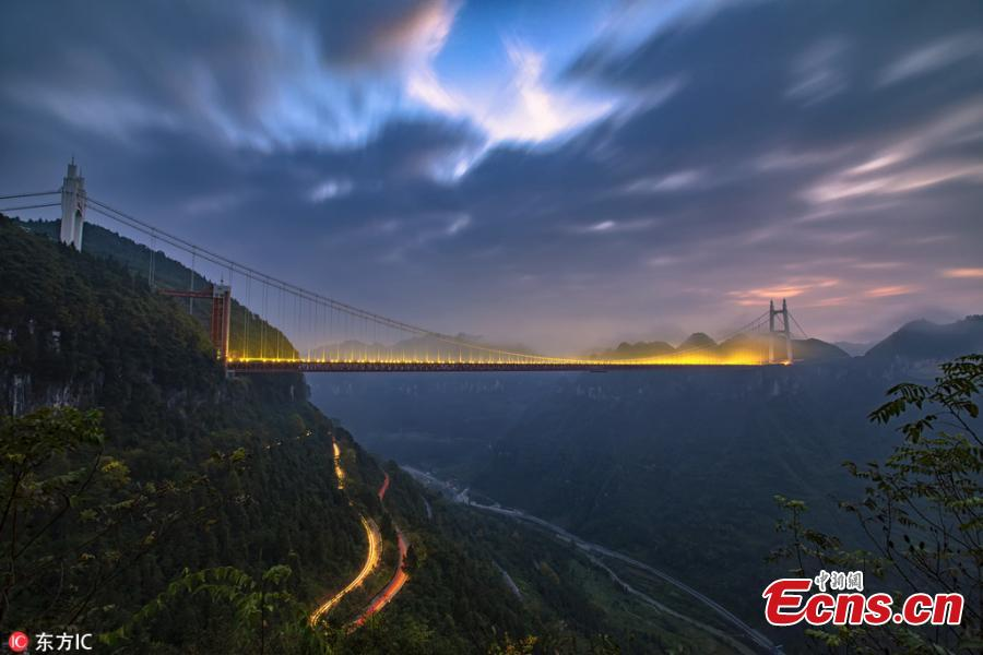 An early morning view of a winding road on a mountain and the Aizhai Bridge in Jishou City, Central China's Hunan Province, Oct. 17, 2018. The suspension bridge was built as part of an expressway from southwest China\'s Chongqing Municipality to Changsha. The bridge links two tunnels 1,176 meters apart and carries traffic 330 meters above the floor of the Dehang Canyon, setting several records including the world\'s highest and longest tunnel-to-tunnel bridge. (Photo/IC)