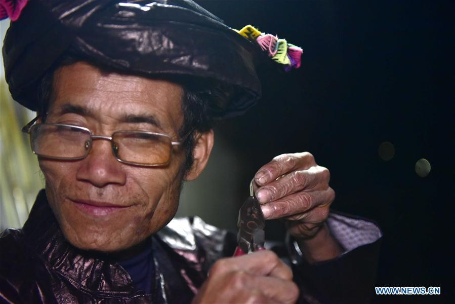 Craftsman Liang Zeguang tests the tone of a reed for Lusheng at Jinying Village in Congjiang County of Miao and Dong Autonomous Prefecture of Qiandongnan, southwest China\'s Guizhou Province, on Oct. 16, 2018. Lusheng is an ethnic musical instrument with multiple bamboo pipes set into a wooden blowing tube. It is popular among the people of some ethnic groups living in southwestern China. Jinying Village, known for making Lusheng, still keeps the traditional Lusheng making techniques which include over 30 steps such as choosing material, installing reed and whittling sound hole. People often play the Lusheng while gathering to celebrate some major festivals. (Xinhua/Wu Dejun)