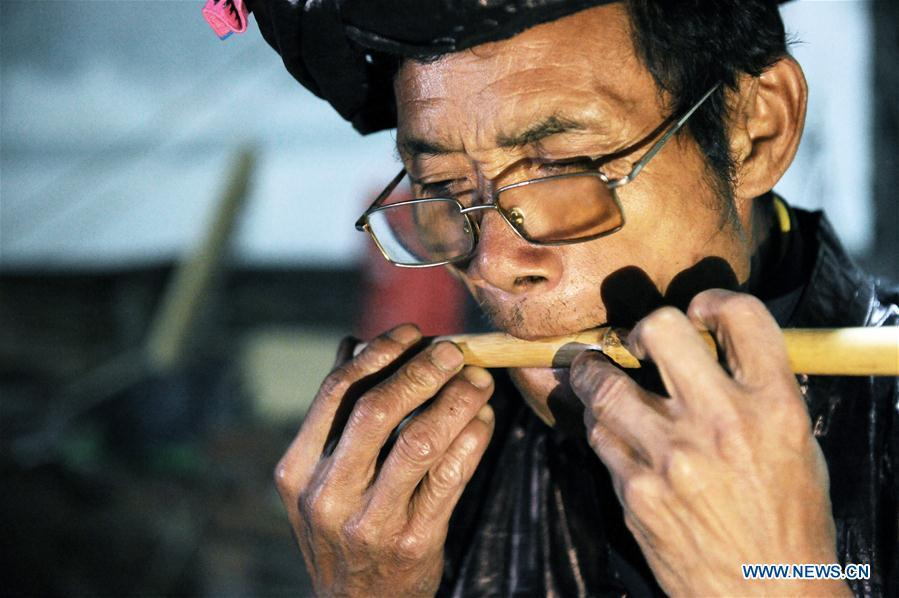 Craftsman Liang Zeguang tests the tone of a reed fitted in a bamboo pipe at Jinying Village in Congjiang County of Miao and Dong Autonomous Prefecture of Qiandongnan, southwest China\'s Guizhou Province, on Oct. 16, 2018. Lusheng is an ethnic musical instrument with multiple bamboo pipes set into a wooden blowing tube. It is popular among the people of some ethnic groups living in southwestern China. Jinying Village, known for making Lusheng, still keeps the traditional Lusheng making techniques which include over 30 steps such as choosing material, installing reed and whittling sound hole. People often play the Lusheng while gathering to celebrate some major festivals. (Xinhua/Yang Wenbin)