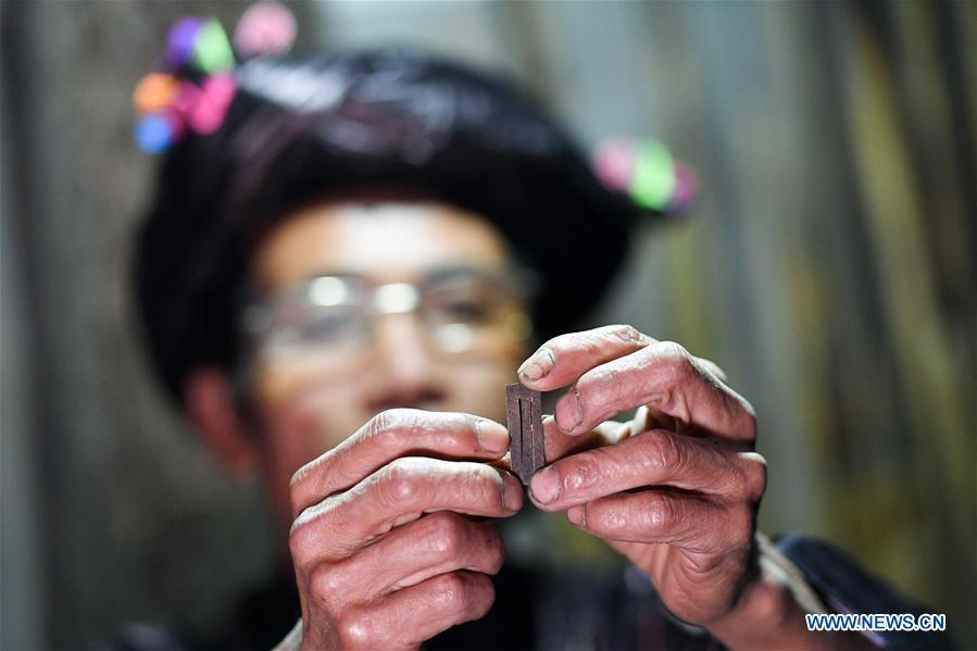 Craftsman Liang Zeguang checks a reed for Lusheng at Jinying Village in Congjiang County of Miao and Dong Autonomous Prefecture of Qiandongnan, southwest China\'s Guizhou Province, on Oct. 16, 2018. Lusheng is an ethnic musical instrument with multiple bamboo pipes set into a wooden blowing tube. It is popular among the people of some ethnic groups living in southwestern China. Jinying Village, known for making Lusheng, still keeps the traditional Lusheng making techniques which include over 30 steps such as choosing material, installing reed and whittling sound hole. People often play the Lusheng while gathering to celebrate some major festivals. (Xinhua/Chen Yehua)