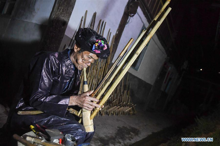 Craftsman Liang Zeguang tests the tone of a finished Lusheng at Jinying Village in Congjiang County of Miao and Dong Autonomous Prefecture of Qiandongnan, southwest China\'s Guizhou Province, on Oct. 16, 2018. Lusheng is an ethnic musical instrument with multiple bamboo pipes set into a wooden blowing tube. It is popular among the people of some ethnic groups living in southwestern China. Jinying Village, known for making Lusheng, still keeps the traditional Lusheng making techniques which include over 30 steps such as choosing material, installing reed and whittling sound hole. People often play the Lusheng while gathering to celebrate some major festivals. (Xinhua/Chen Yehua)