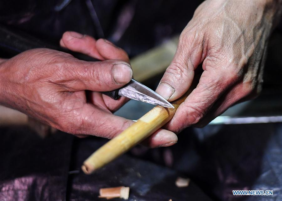 Craftsman Liang Zeguang whittles a sound hole on the tube of Lusheng at Jinying Village in Congjiang County of Miao and Dong Autonomous Prefecture of Qiandongnan, southwest China\'s Guizhou Province, on Oct. 16, 2018. Lusheng is an ethnic musical instrument with multiple bamboo pipes set into a wooden blowing tube. It is popular among the people of some ethnic groups living in southwestern China. Jinying Village, known for making Lusheng, still keeps the traditional Lusheng making techniques which include over 30 steps such as choosing material, installing reed and whittling sound hole. People often play the Lusheng while gathering to celebrate some major festivals. (Xinhua/Chen Yehua)