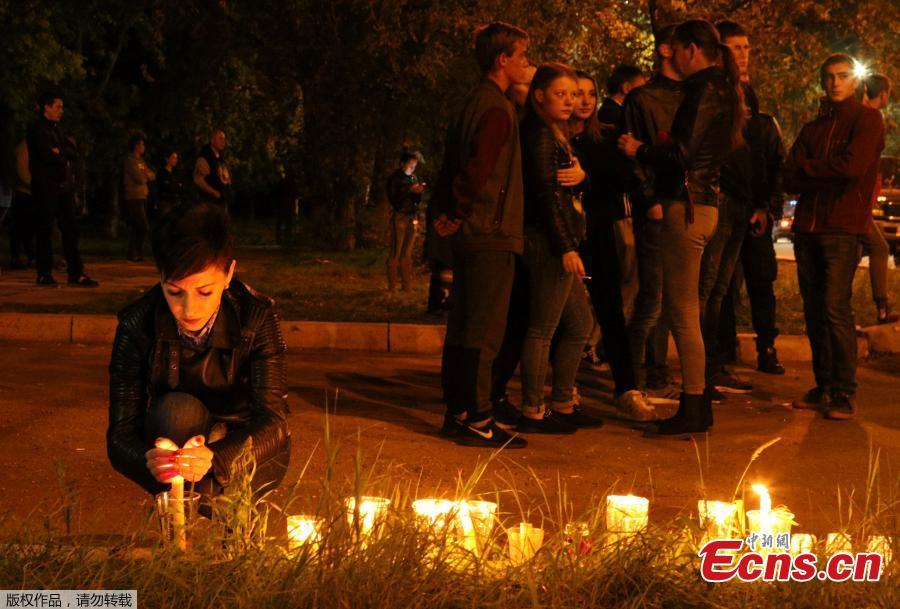 A woman lights a candle at a makeshift memorial near the scene of a fatal attack on a college in the port city of Kerch, Crimea, Oct. 17, 2018. At least 19 people have been killed and dozens injured in a mass shooting at the college. (Photo/Agencies)