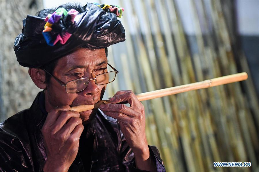 Craftsman Liang Zeguang tests the tone of a reed fitted in a bamboo pipe at Jinying Village in Congjiang County of Miao and Dong Autonomous Prefecture of Qiandongnan, southwest China\'s Guizhou Province, on Oct. 16, 2018. Lusheng is an ethnic musical instrument with multiple bamboo pipes set into a wooden blowing tube. It is popular among the people of some ethnic groups living in southwestern China. Jinying Village, known for making Lusheng, still keeps the traditional Lusheng making techniques which include over 30 steps such as choosing material, installing reed and whittling sound hole. People often play the Lusheng while gathering to celebrate some major festivals. (Xinhua/Chen Yehua)
