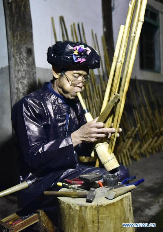 Craftsman Liang Zeguang tests the tone of a finished Lusheng at Jinying Village in Congjiang County of Miao and Dong Autonomous Prefecture of Qiandongnan, southwest China\'s Guizhou Province, on Oct. 16, 2018. Lusheng is an ethnic musical instrument with multiple bamboo pipes set into a wooden blowing tube. It is popular among the people of some ethnic groups living in southwestern China. Jinying Village, known for making Lusheng, still keeps the traditional Lusheng making techniques which include over 30 steps such as choosing material, installing reed and whittling sound hole. People often play the Lusheng while gathering to celebrate some major festivals. (Xinhua/Wu Dejun)