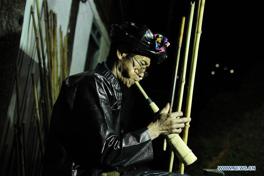 Craftsman Liang Zeguang tests the tone of a finished Lusheng at Jinying Village in Congjiang County of Miao and Dong Autonomous Prefecture of Qiandongnan, southwest China\'s Guizhou Province, on Oct. 16, 2018. Lusheng is an ethnic musical instrument with multiple bamboo pipes set into a wooden blowing tube. It is popular among the people of some ethnic groups living in southwestern China. Jinying Village, known for making Lusheng, still keeps the traditional Lusheng making techniques which include over 30 steps such as choosing material, installing reed and whittling sound hole. People often play the Lusheng while gathering to celebrate some major festivals. (Xinhua/Yang Wenbin)