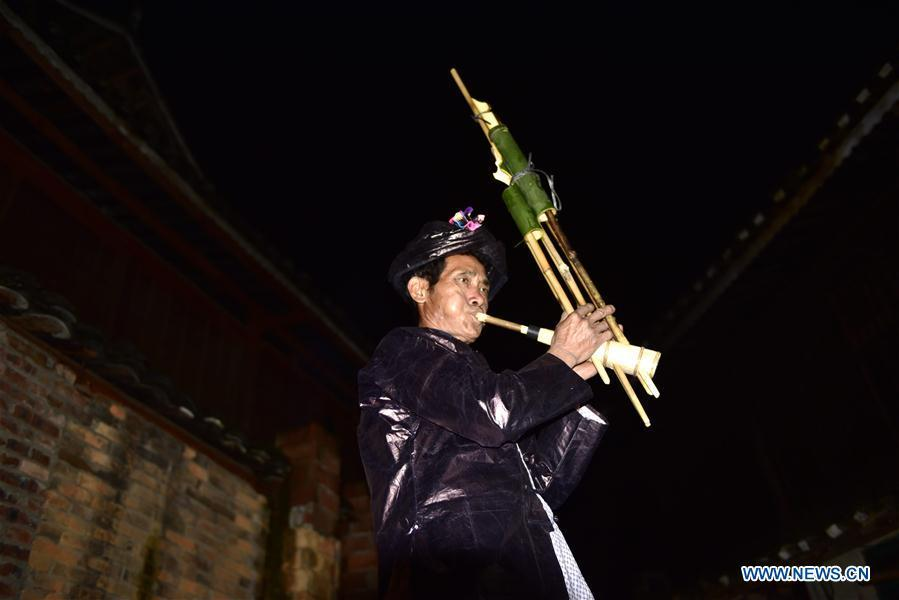 Craftsman Liang Zeguang tries a finished Lusheng at Jinying Village in Congjiang County of Miao and Dong Autonomous Prefecture of Qiandongnan, southwest China\'s Guizhou Province, on Oct. 16, 2018. Lusheng is an ethnic musical instrument with multiple bamboo pipes set into a wooden blowing tube. It is popular among the people of some ethnic groups living in southwestern China. Jinying Village, known for making Lusheng, still keeps the traditional Lusheng making techniques which include over 30 steps such as choosing material, installing reed and whittling sound hole. People often play the Lusheng while gathering to celebrate some major festivals. (Xinhua/Wu Dejun)
