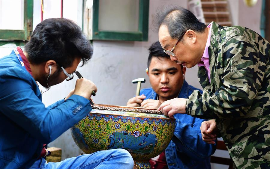 Lin Hui instructs workers on an enamelwork in Putian, southeast China\'s Fujian Province, Oct. 18, 2018. Lin Hui is an intangible cultural heritage inheritor of Lin\'s cloisonne, or copper padding thread weaving enamel, a kind of traditional Chinese handicrafts. (Xinhua/Wei Peiquan)