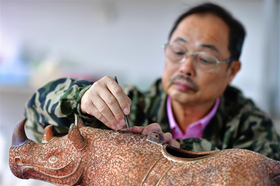 Lin Hui works on an enamel rhino in Putian, southeast China\'s Fujian Province, Oct. 18, 2018. Lin Hui is an intangible cultural heritage inheritor of Lin\'s cloisonne, or copper padding thread weaving enamel, a kind of traditional Chinese handicrafts. (Xinhua/Wei Peiquan)