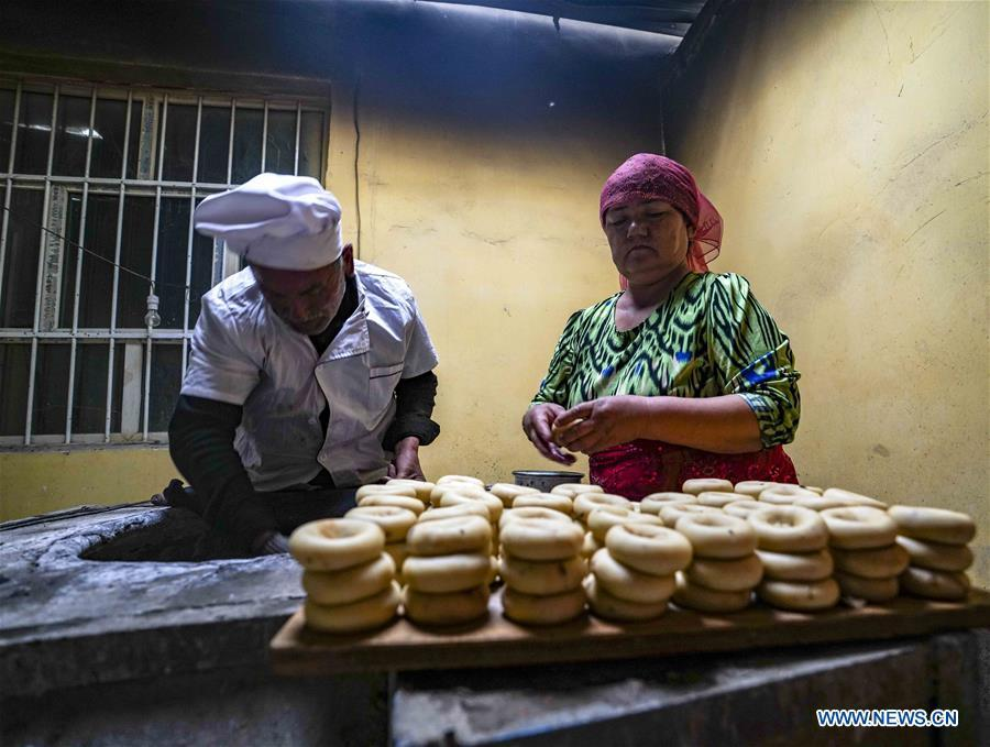 Yusup Tapuhan (L) and his wife bake butter naan in Yuli County of the Mongolian Autonomous Prefecture of Bayingolin, northwest China\'s Xinjiang Uygur Autonomous Region, Oct. 17, 2018. Yusup Tapuhan launched his butter naan business in 2000. The making of this popular pastry has been a tradition in Yuli County. In 2017, a dedicated local naan guild was established to help those in the business optimize profit. Yusup, who is 63, became one of the guild\'s earliest members. With the help of his family, Yusup can make 50 kilograms of butter naan and earn 500 yuan (72 U.S. dollars) a day. (Xinhua/Zhao Ge)