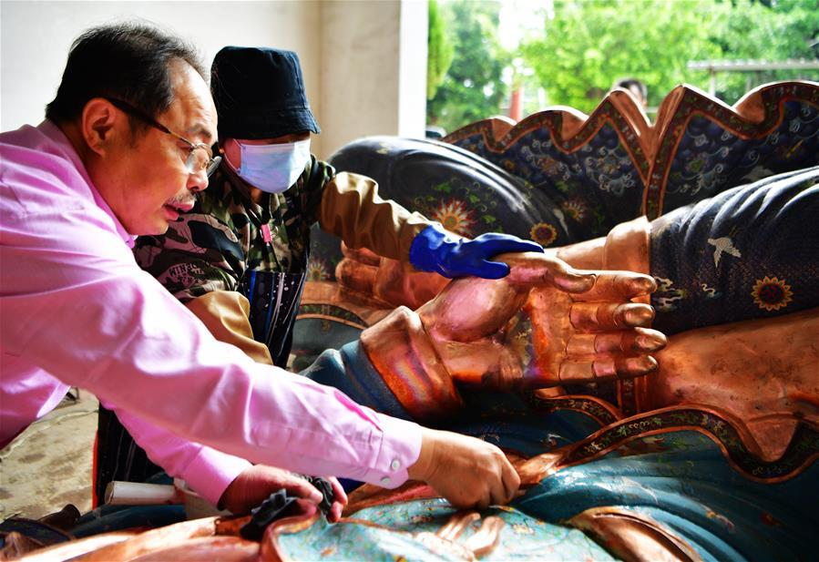 Lin Hui instructs workers on polishing enamelworks in Putian, southeast China\'s Fujian Province, Oct. 18, 2018. Lin Hui is an intangible cultural heritage inheritor of Lin\'s cloisonne, or copper padding thread weaving enamel, a kind of traditional Chinese handicrafts. (Xinhua/Wei Peiquan)