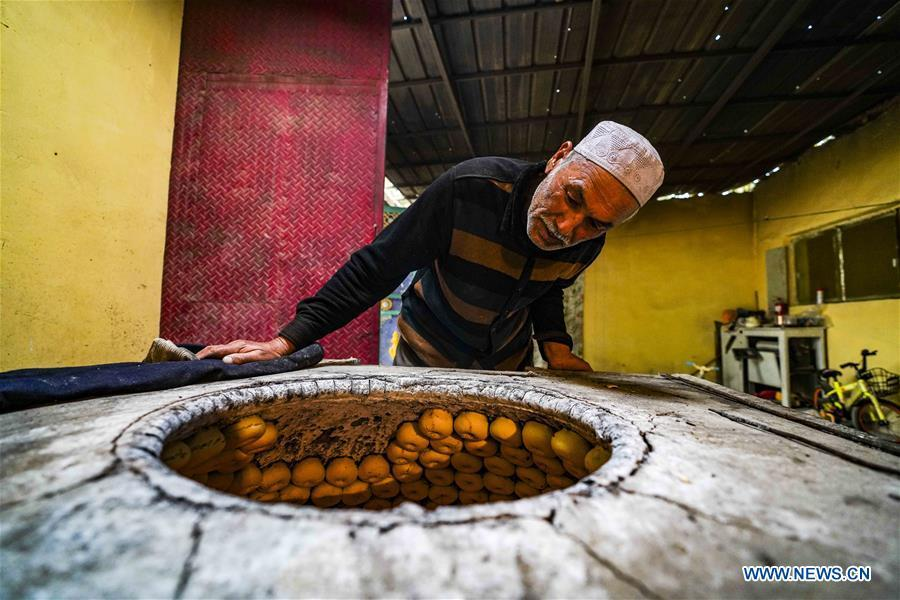 Yusup Tapuhan (C) makes butter naan at home in Yuli County of the Mongolian Autonomous Prefecture of Bayingolin, northwest China\'s Xinjiang Uygur Autonomous Region, Oct. 17, 2018. Yusup Tapuhan launched his butter naan business in 2000. The making of this popular pastry has been a tradition in Yuli County. In 2017, a dedicated local naan guild was established to help those in the business optimize profit. Yusup, who is 63, became one of the guild\'s earliest members. With the help of his family, Yusup can make 50 kilograms of butter naan and earn 500 yuan (72 U.S. dollars) a day. (Xinhua/Zhao Ge)