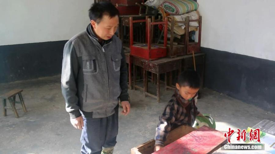 Lai Zhenyuan watches as his only student Wang Longze packs his bag after school in Xuanhan County, Southwest China's Sichuan Province in mid-October. Four students left to study at a larger school this autumn semester, leaving only Wang from a poor family to study there. Wang's father is disabled and suffers from disease, and his mother died not long after he was born. Lai has decided to stay in the school to teach Wang. (Photo: China News Service/Zhong Xin)