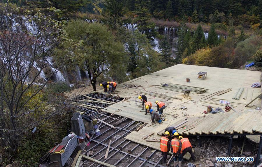 In this aerial photo taken on Oct. 18, 2018, workers repair a lookout platform at the Jiuzhaigou Valley Scenic Area in Jiuzhaigou County, southwest China\'s Sichuan Province. The magnitude-7.0 earthquake that hit here on Aug. 8, 2017 and the flooding of this summer caused damages of various degrees to the Jiuzhaigou Valley Scenic Area, which has been temporarily closed since July for renovation. (Xinhua/Deng Jian)