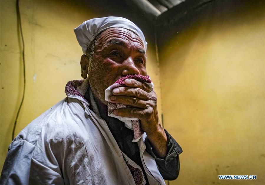 Yusup Tapuhan wipes sweat from his face while baking butter naan in Yuli County of the Mongolian Autonomous Prefecture of Bayingolin, northwest China\'s Xinjiang Uygur Autonomous Region, Oct. 17, 2018. Yusup Tapuhan launched his butter naan business in 2000. The making of this popular pastry has been a tradition in Yuli County. In 2017, a dedicated local naan guild was established to help those in the business optimize profit. Yusup, who is 63, became one of the guild\'s earliest members. With the help of his family, Yusup can make 50 kilograms of butter naan and earn 500 yuan (72 U.S. dollars) a day. (Xinhua/Zhao Ge)