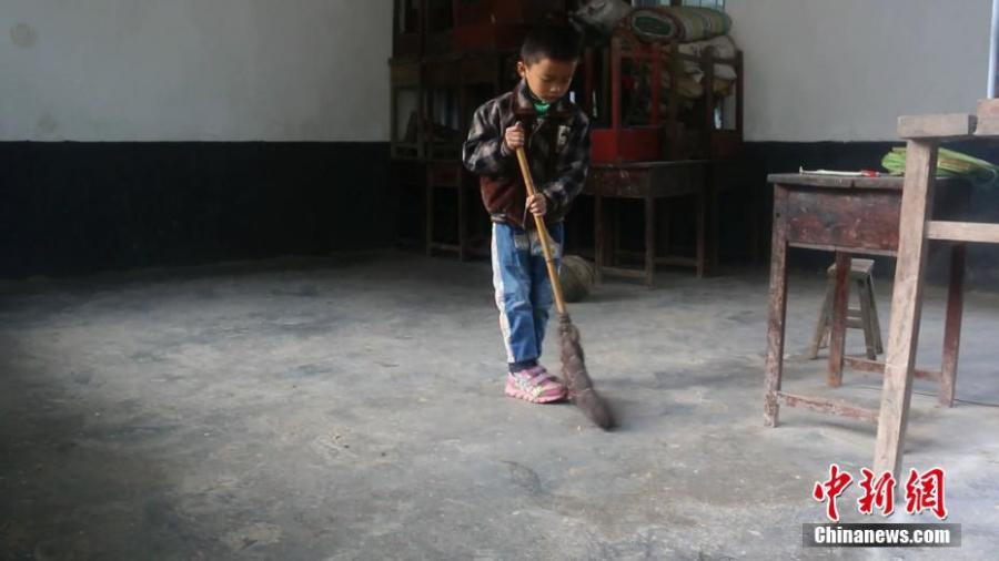 Wang Longze helps clean the classroom at an elementary school on a mountain in Xuanhan County, Southwest China's Sichuan Province in mid-October. Four students left to study at a larger school this autumn semester, leaving only Wang from a poor family to study there. Wang's father is disabled and suffers from disease, and his mother died not long after he was born. Lai has decided to stay in the school to teach Wang. (Photo: China News Service/Zhong Xin)