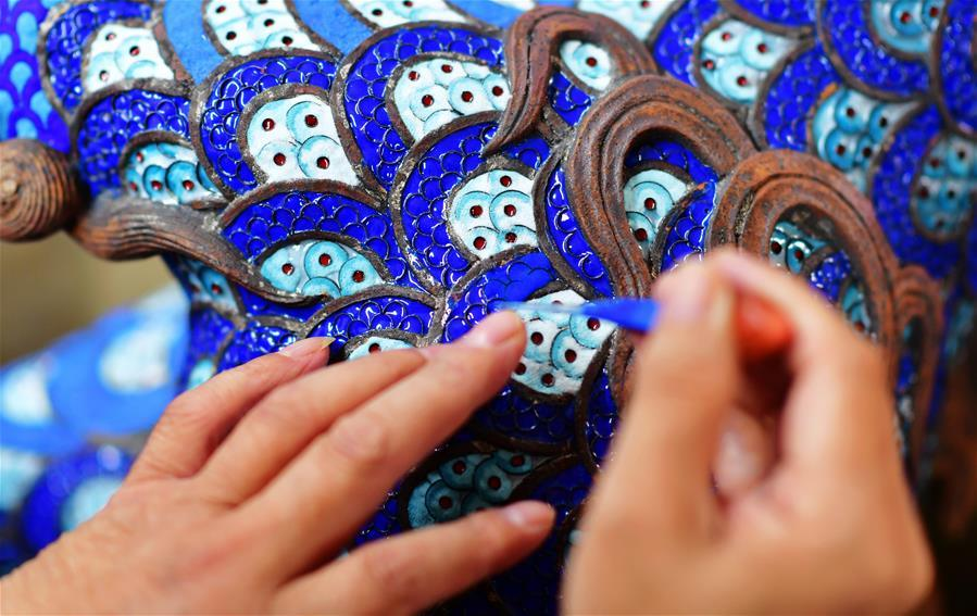 Lin Hui works on an enamelwork in Putian, southeast China\'s Fujian Province, Oct. 18, 2018. Lin Hui is an intangible cultural heritage inheritor of Lin\'s cloisonne, or copper padding thread weaving enamel, a kind of traditional Chinese handicrafts. (Xinhua/Wei Peiquan)