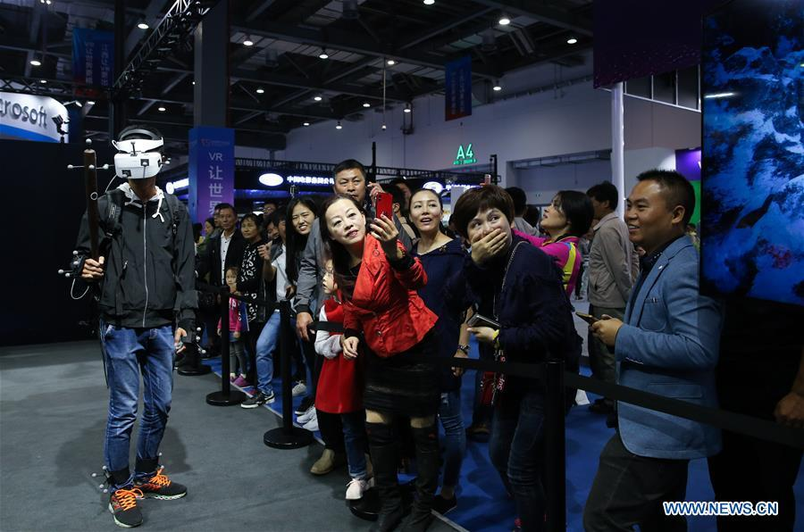 A visitor (L) plays VR (virtual reality) game during the 2018 World Conference on VR Industry in Nanchang, east China\'s Jiangxi Province, Oct. 19, 2018. The 2018 World Conference on VR Industry opened here on Friday. The three-day event attracts more than 150 global exhibitors in the virtual reality field. (Xinhua/Pan Siwei)