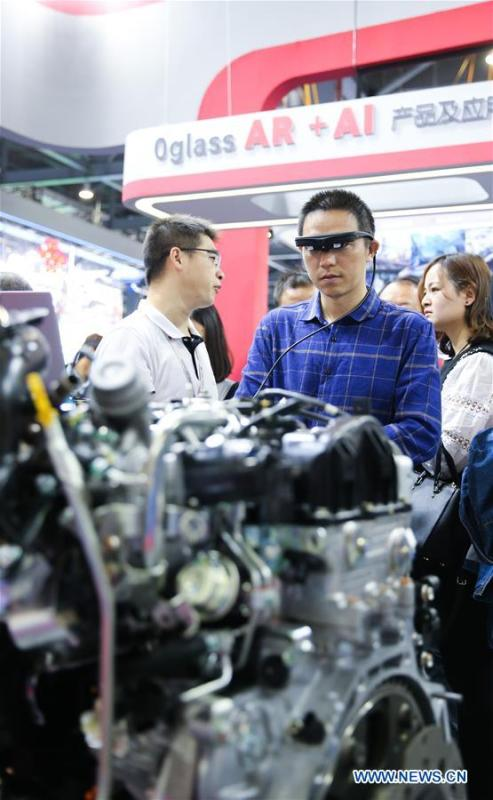 A visitor (2nd R) learns about car motor assembling via a pair of AR (augmented reality) glasses during the 2018 World Conference on VR Industry in Nanchang, east China\'s Jiangxi Province, Oct. 19, 2018. The 2018 World Conference on VR Industry opened here on Friday. The three-day event attracts more than 150 global exhibitors in the virtual reality field. (Xinhua/Pan Siwei)