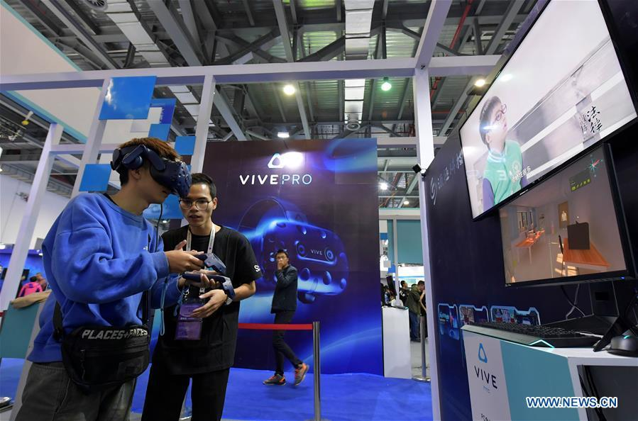 A visitor (L) tries a VR (virtual reality) device during the 2018 World Conference on VR Industry in Nanchang, east China\'s Jiangxi Province, Oct. 19, 2018. The 2018 World Conference on VR Industry opened here on Friday. The three-day event attracts more than 150 global exhibitors in the virtual reality field. (Xinhua/Peng Zhaozhi)