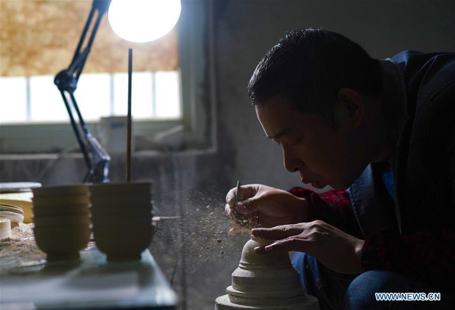 A craftsman named Jiang Peihua polishes the earthen body of an eggshell porcelain in Jingdezhen, east China\'s Jiangxi Province, on Oct. 19, 2018. Eggshell porcelain, one of the traditional porcelains produced in \
