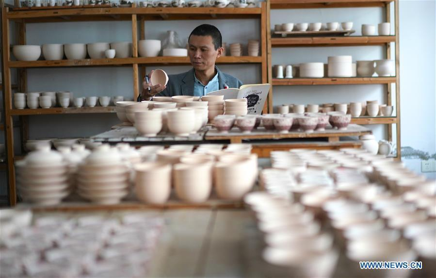 A craftsman named Zeng Lei counts a batch of finished eggshell porcelains in Jingdezhen, east China\'s Jiangxi Province, on Oct. 19, 2018. Eggshell porcelain, one of the traditional porcelains produced in \