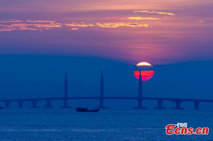 A view of the Hong Kong-Zhuhai-Macao Bridge at sunrise from Qinglv Road in Zhuhai City, South China's Guangdong Province, Oct. 22, 2018. The world\'s longest sea bridge will start operation on Oct. 24, further integrating cities in the Pearl River Delta. (Photo: China News Service/Zhang Wei)