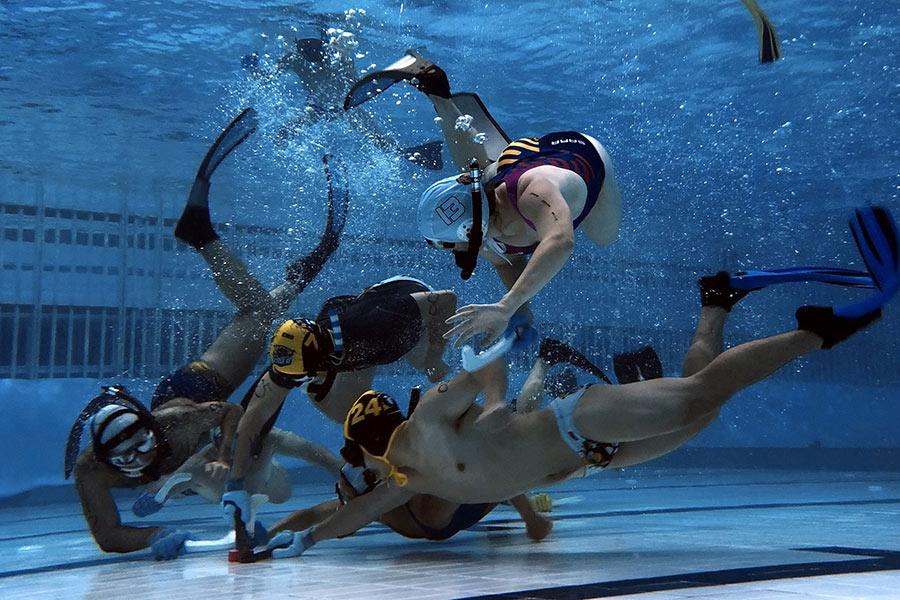 Players compete in an underwater hockey game in Chongqing. (Photo provided to China Daily)  Underwater hockey, a sport most Chinese have never heard of, is becoming popular among swimmers and divers in a dozen big cities, including Beijing, Shanghai and Guangzhou.  Players wear diving masks, snorkels and fins, and carry a short stick in one hand for playing the puck in a swimming pool. Two teams of up to 10 players compete, with six players in each team in play at any one time. In club matches, two of the six must be women.  The sport originated in England in 1954 when a group of divers wanted to keep active in the cold winter months. It is now a worldwide sport, mainly played in the United Kingdom, Australia, Canada, France, the Netherlands, New Zealand, South Africa and the United States.  In China, the sport was originally played by foreign expats and young Chinese who had returned from overseas. Later, more Chinese swimmers started to join in.  There are now two underwater hockey clubs in Chongqing, a metropolis in southwestern China, with the first one formed last year and the second one this year.