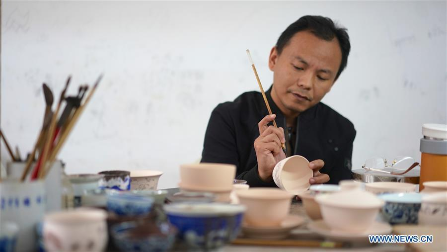 A craftsman named Liu Zhen paints on the body of an eggshell porcelain in Jingdezhen, east China\'s Jiangxi Province, on Oct. 19, 2018. Eggshell porcelain, one of the traditional porcelains produced in \