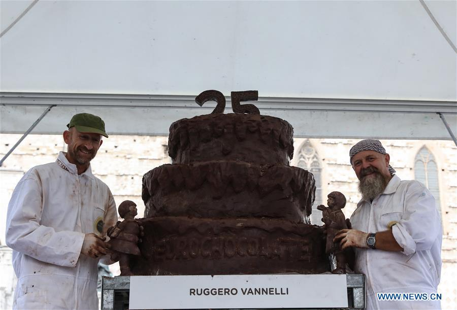 Artists pose for photos with the chocolate sculpture they created during the 25th international chocolate festival \