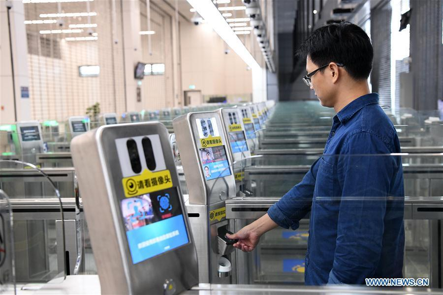 A staff worker demonstrates passing through the automatic channel in Zhuhai Port of Hong Kong-Zhuhai-Macao Bridge in Zhuhai, south China\'s Guangdong Province, Oct. 18, 2018. Customs clearance between Macao and Zhuhai will be carried out on a \