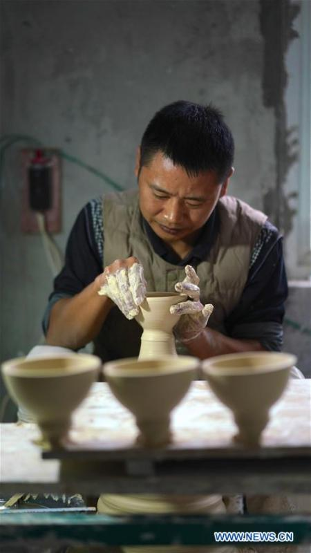A craftsman named Zhang Rong makes the earthen body of an eggshell porcelain in Jingdezhen, east China\'s Jiangxi Province, on Oct. 19, 2018. Eggshell porcelain, one of the traditional porcelains produced in \