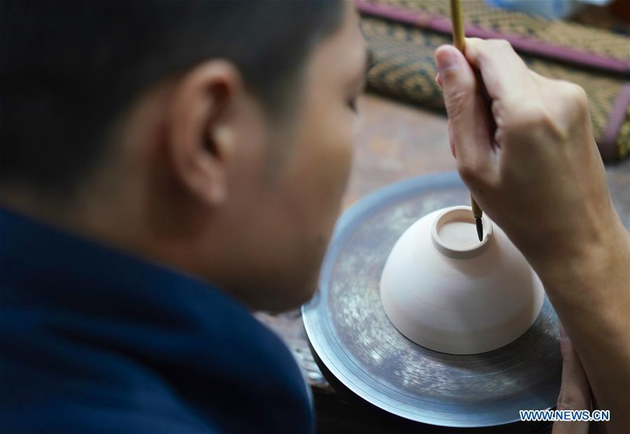 A craftsman named Peng Yongliang edges the bottom of an eggshell porcelain body in Jingdezhen, east China\'s Jiangxi Province, on Oct. 19, 2018. Eggshell porcelain, one of the traditional porcelains produced in \