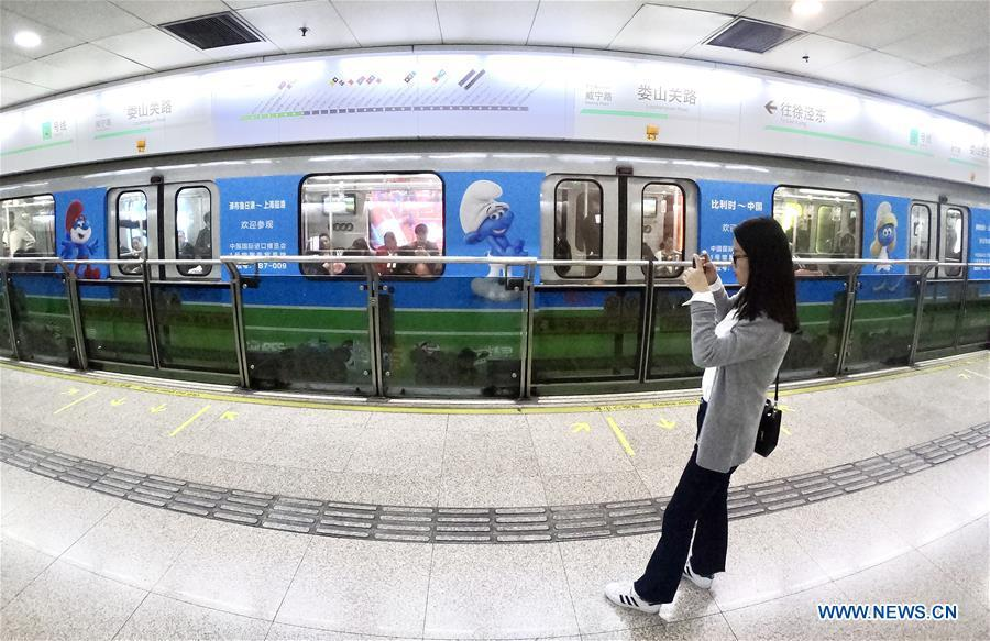 A passenger takes photos of a China-Belgium theme train of Shanghai Metro Line 2 bearing character images from Belgian comic \