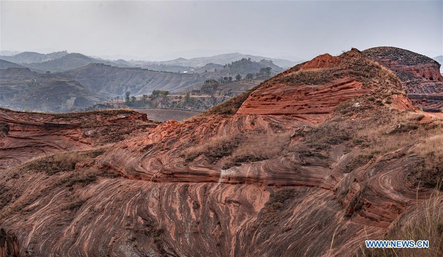 Photo taken on Oct. 21, 2018 shows a view of Danxia landform at Wangjiawan of Pingqiao Town in Ansai District of Yan\'an, northwest China\'s Shaanxi Province. Danxia landform is a unique type of geomorphology formed from red-colored sandstones and characterized by steep cliffs. (Xinhua/Tao Ming)