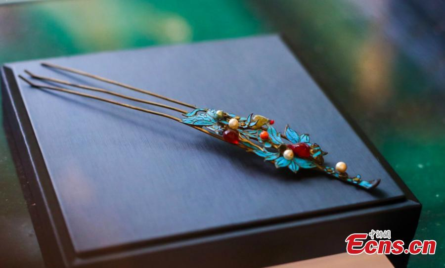 Artist Ma Jingji shows 30 pieces of Diancui works he has collected or created at an exhibition in Chongqing, Oct. 22, 2018. Diancui, or dotting with kingfishers, is a painstakingly time-consuming and precise practice of inlaying iridescent kingfisher feathers into accessories for the rich and noble. Craftsmen apply the shimmering feathers to jewelry, hairpins, bracelets, brooches, fans, and landscape panels. Instead of kingfisher feathers, goose feathers and ribbons are used nowadays to make art creations with diancui skills.(Photo: China News Service/Zhong Xin)