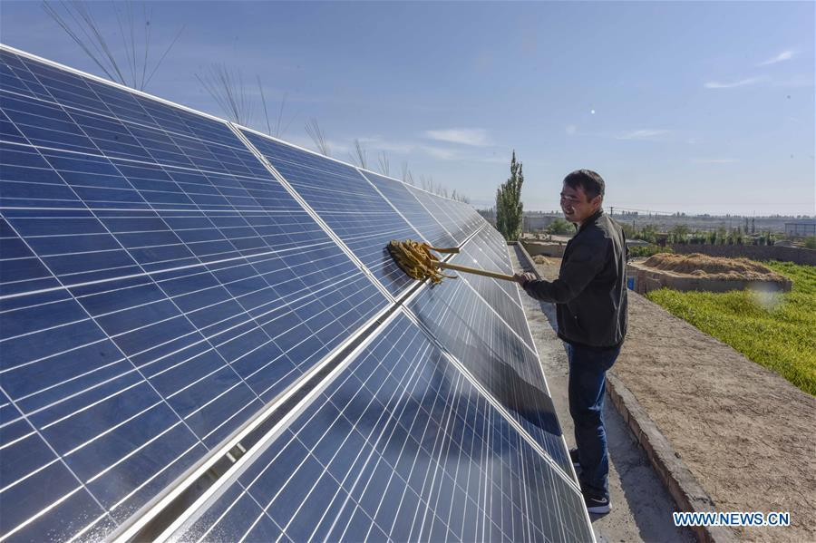 Villager Pan Linqi cleans solar panels in Hami, northwest China\'s Xinjiang Uygur Autonomous Region, Sept. 21, 2018. Xinjiang has seen a surge in the electricity generation from clean energy. According to State Grid Xinjiang Electric Power Co., Ltd., wind and solar power generated 27.81 billion and 9.07 billion kilowatt hours (kwh) of electricity, respectively, in the first nine months of 2018 in the region. With abundant wind and solar resources, Xinjiang is a pioneer in using new energy in China, with installed new-energy capacity having exceeded 27 million kilowatts so far. (Xinhua/Zhao Ge)