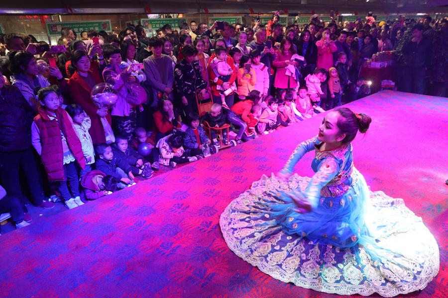 People enjoy the dance performance at the night food market in Hotan city in Northwest China\'s Xinjiang Uygur autonomous region, Oct. 22, 2018.   There is so much more than mouth-watering traditional Uygur food at the night food market in Hotan city in Northwest China\'s Xinjiang Uygur autonomous region, which is always packed with people every night. The hospitable Uygurs will invite visitors to join their dances and enjoy their culture. (Photo/chinadaily.com.cn)
