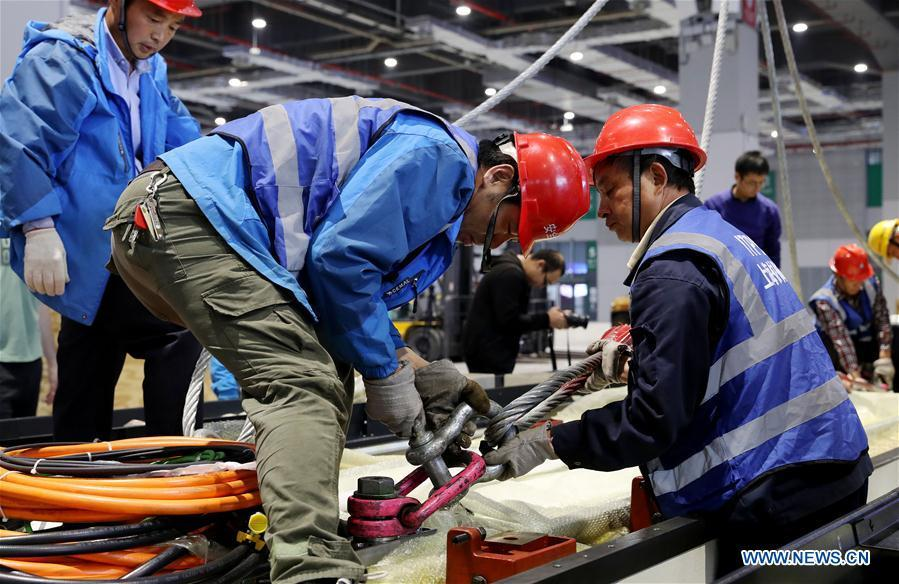 Workers make preparation for lifting operation of Taurus milling machine in Shanghai, east China, Oct. 22, 2018. Preliminary assembly of the milling machine, which will be the largest exhibit to be on show at China\'s upcoming import expo, was finished here on Monday. The exhibit is expected to cover 200 square meters of exhibiting space during the expo, which is scheduled to be held in Shanghai on Nov. 5-10. (Xinhua/Fang Zhe)