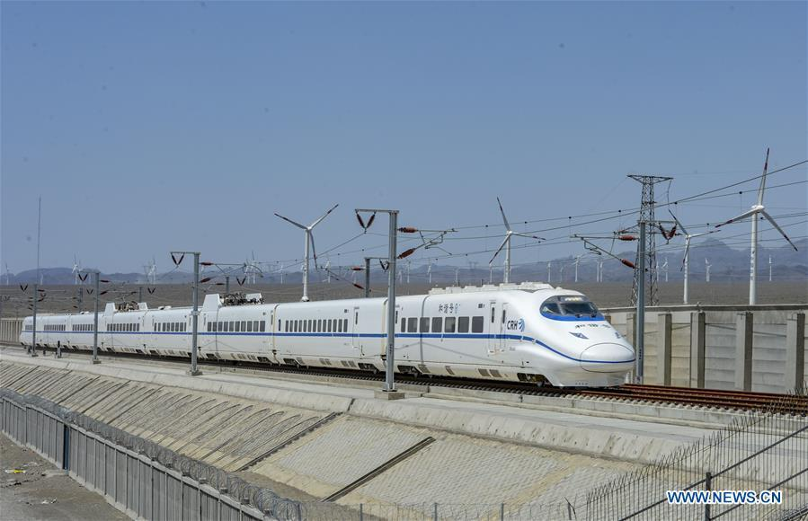 A bullet train runs past a wind power plant in Urumqi, northwest China\'s Xinjiang Uygur Autonomous Region, May 29, 2014. Xinjiang has seen a surge in the electricity generation from clean energy. According to State Grid Xinjiang Electric Power Co., Ltd., wind and solar power generated 27.81 billion and 9.07 billion kilowatt hours (kwh) of electricity, respectively, in the first nine months of 2018 in the region. With abundant wind and solar resources, Xinjiang is a pioneer in using new energy in China, with installed new-energy capacity having exceeded 27 million kilowatts so far. (Xinhua/Zhao Ge)