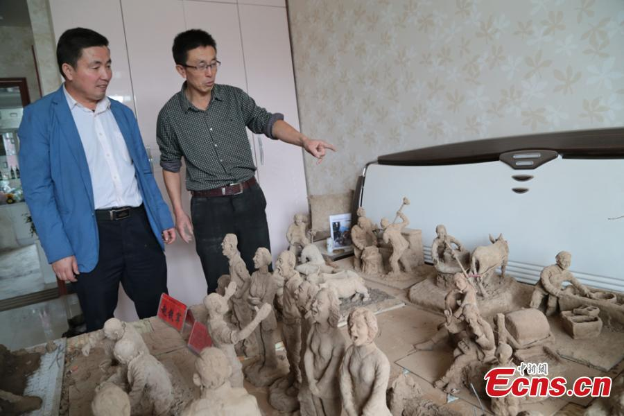 Clay sculpture enthusiast Zhao Tiejun shows his creations featuring past rural life and farming traditions in his home in Pingliang City, Northwest China's Gansu Province, Oct. 23, 2018. Zhao has been fascinated with the hobby of making clay figurines for two decades as he believes the handicraft can help younger generation learn about the countryside life now increasingly transformed. (Photo: China News Service/Zheng Bing)