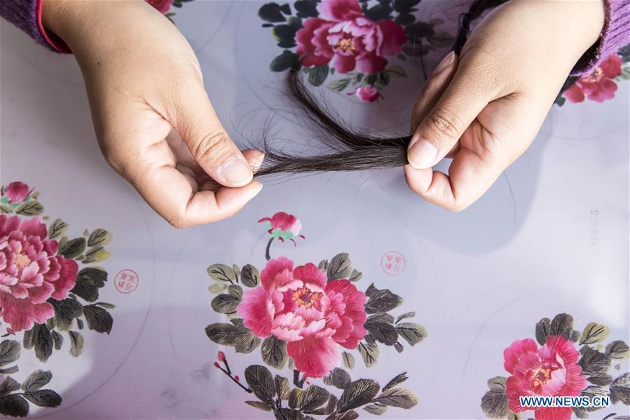 A local artist selects hairs for embroidery works in Dongtai, east China\'s Jiangsu Province, Oct. 22, 2018. (Xinhua/Xiang Zhonglin)