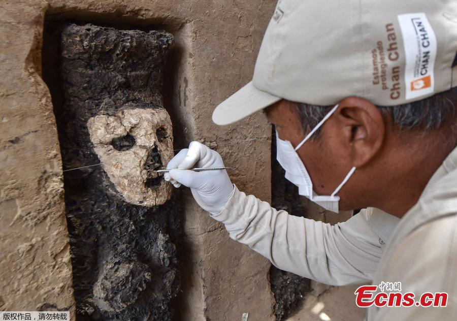An archaeologist cleans a wooden mask of the Mochica culture at Chan Chan archeological complex in Trujillo, Peru, Oct. 22, 2018. Archeologists in Peru have found 20 800-year-old wooden statues in the largest pre-Columbian site in the Americas, Culture Minister, Patricia Balbuena and researchers revealed on Monday. (Photo/Agencies)