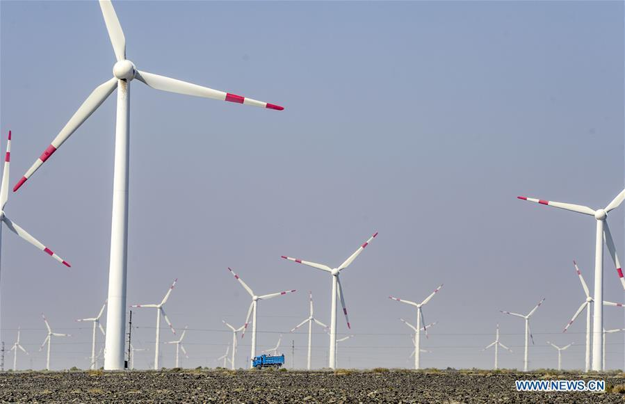 A vehicle runs across a wind power plant in Urumqi, northwest China\'s Xinjiang Uygur Autonomous Region, Sept. 18, 2018. Xinjiang has seen a surge in the electricity generation from clean energy. According to State Grid Xinjiang Electric Power Co., Ltd., wind and solar power generated 27.81 billion and 9.07 billion kilowatt hours (kwh) of electricity, respectively, in the first nine months of 2018 in the region. With abundant wind and solar resources, Xinjiang is a pioneer in using new energy in China, with installed new-energy capacity having exceeded 27 million kilowatts so far. (Xinhua/Zhao Ge)