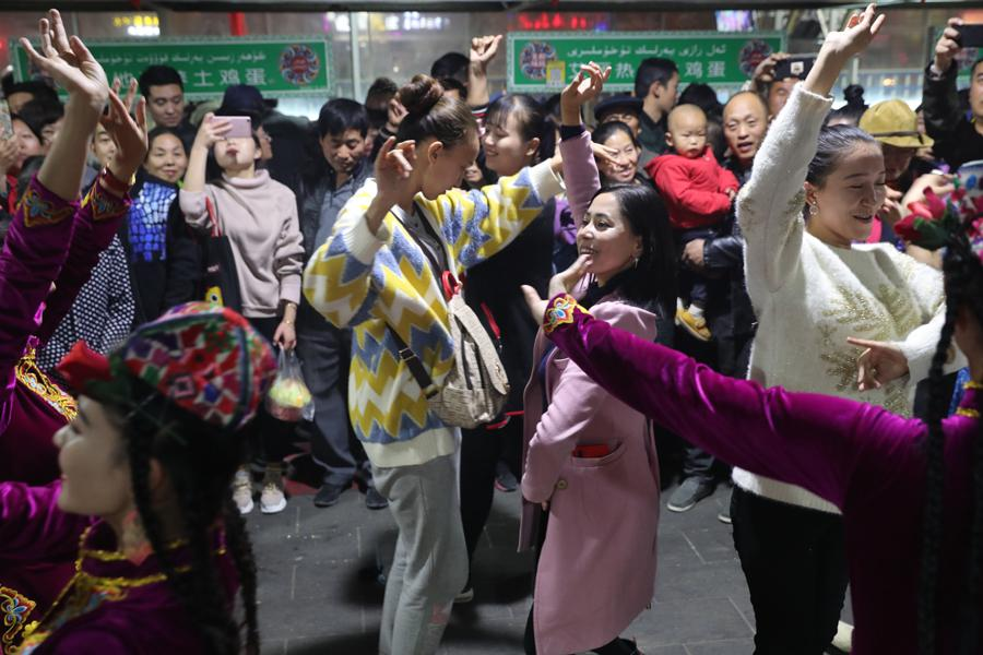 People dance at the night food market in Hotan city in Northwest China\'s Xinjiang Uygur autonomous region, Oct. 22, 2018. (Photo/chinadaily.com.cn)