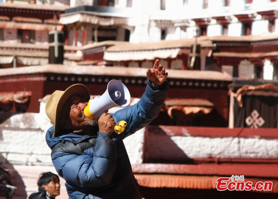 A retiree from the Potala Palace administration office helps workers during annual renovation work following the end of the rainy season in Lhasa, Southwest China's Tibet Autonomous Region, Oct. 23, 2018. The painting work will take one week. (Photo: China News Service/Zhao yan)
