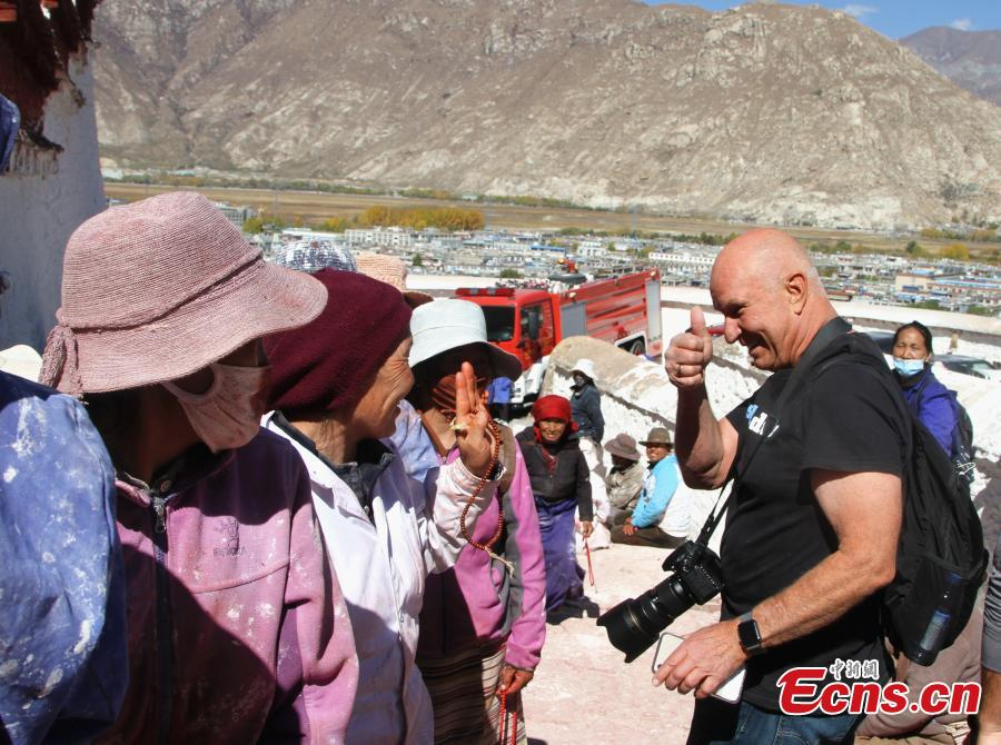 A tourist from the United States greets pilgrims to the Potala Palace in Lhasa, Southwest China's Tibet Autonomous Region, Oct. 23, 2018. The painting work will take one week. (Photo: China News Service/Zhao yan)