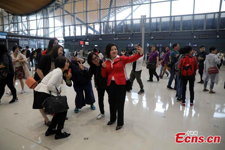 Passengers pose in Hong Kong before boarding coaches that will pass over the Hong Kong-Zhuhai-Macao Bridge Oct. 24, 2018. (Photo: China News Service/Sheung Man Mak)